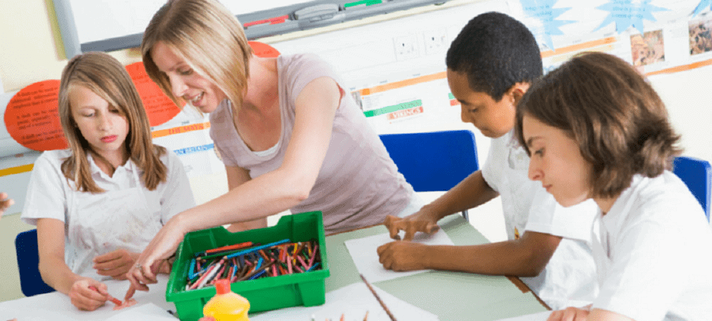Occupational Therapist helping kids to hold crayons