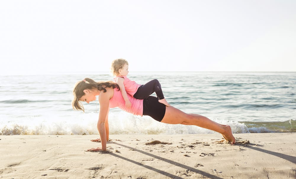 Yoga Studios Gold Coast family workout - mother and daughter doing exercises on beach. Mom and child working out on seaside in the morning. Healthy lifestyle concept