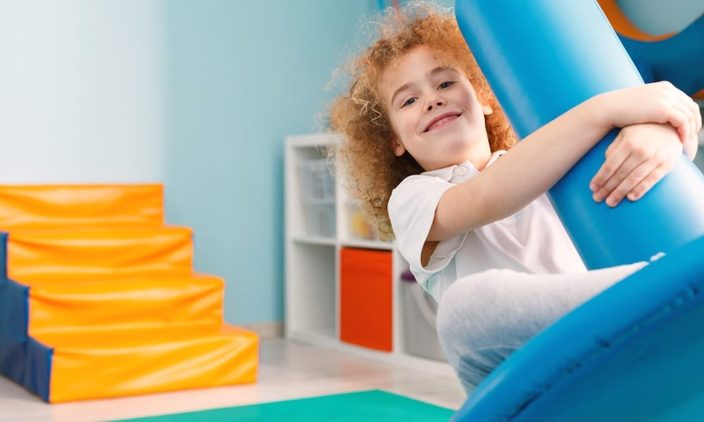 Occupational Therapist Gold Coast Happy boy using blue disc swing for therapy