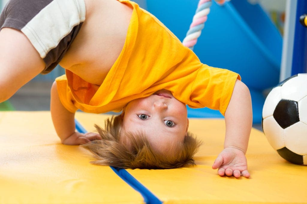 baby standing upside down on gym mat gymnastics calculated risks