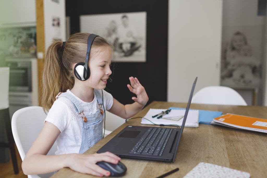 Child studying at home waving to her online tutor