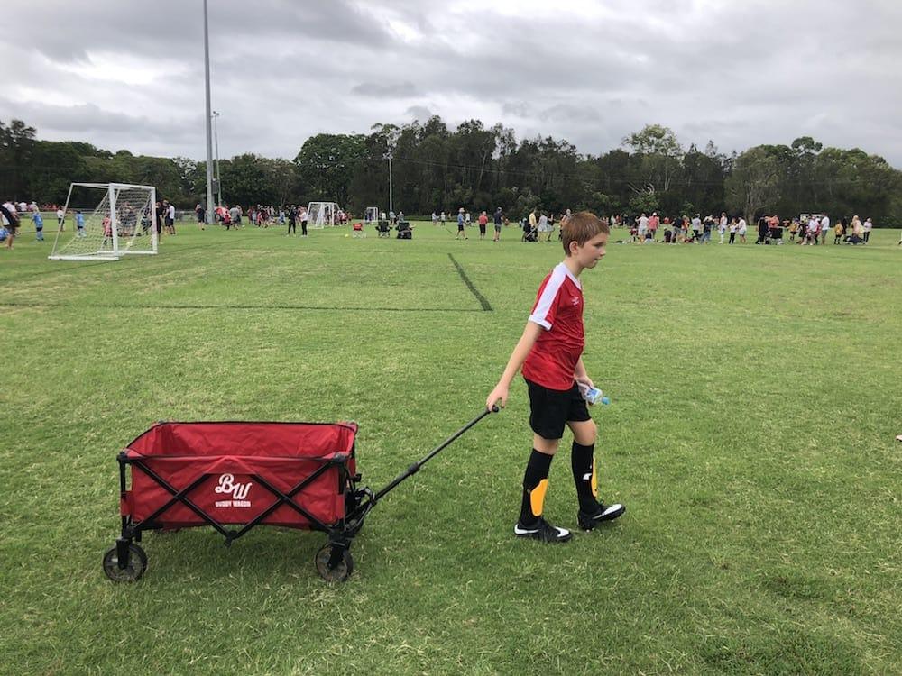 Boy dragging red Buddy Wagon at soccer match
