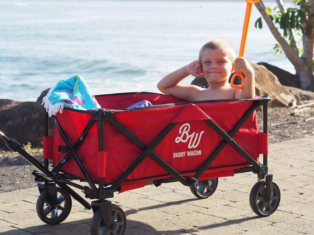 Boy being dragged in red Buddy Wagon