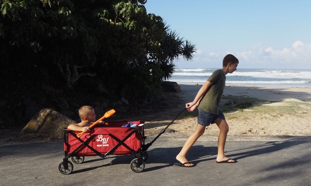Brother dragging toddler in red Buddy Wagon