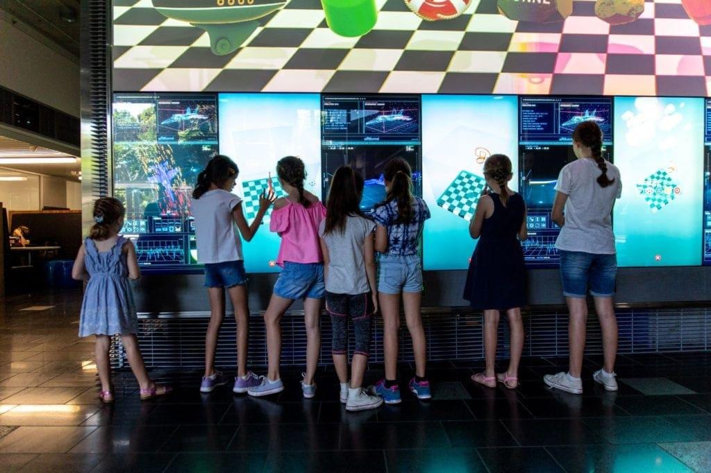 qut school holiday activities girls in front of big screen
