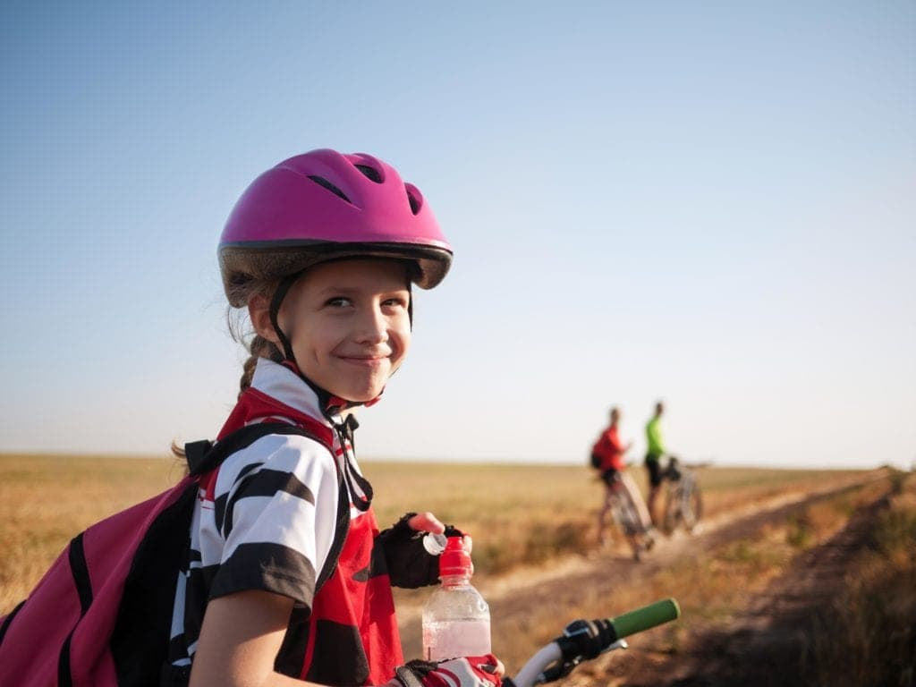 Girl Smiling Back at Camera on Bike Ride