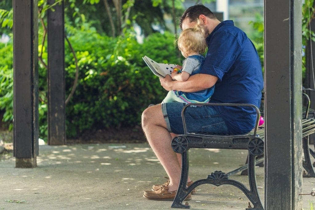 Dad reads to baby outside