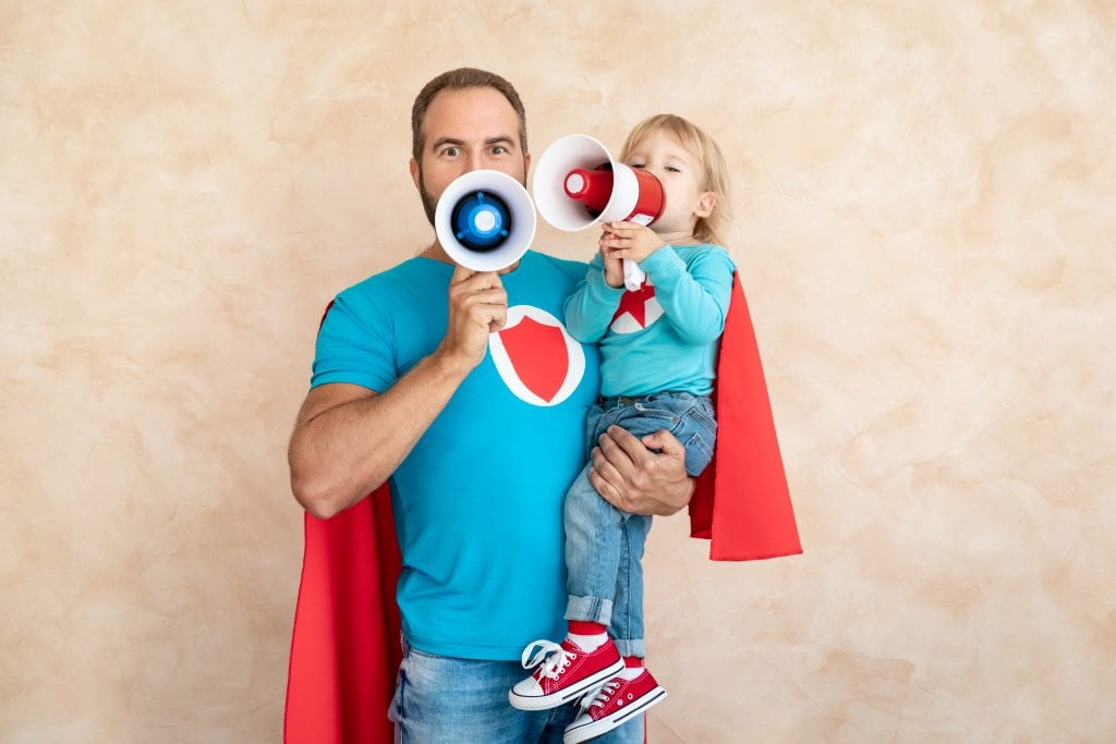 Father and child as superheroes with loud speakers